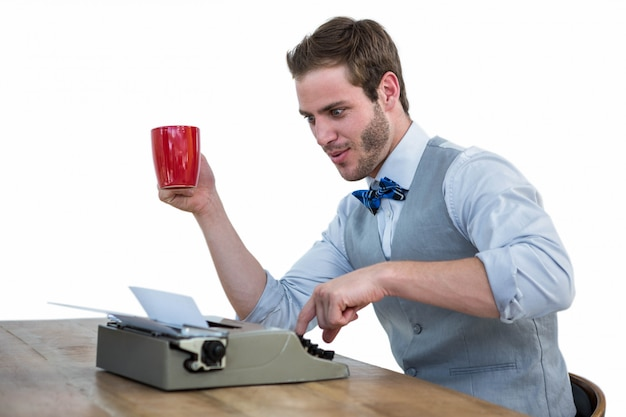 Gut aussehender mann, der altmodische schreibmaschine verwendet