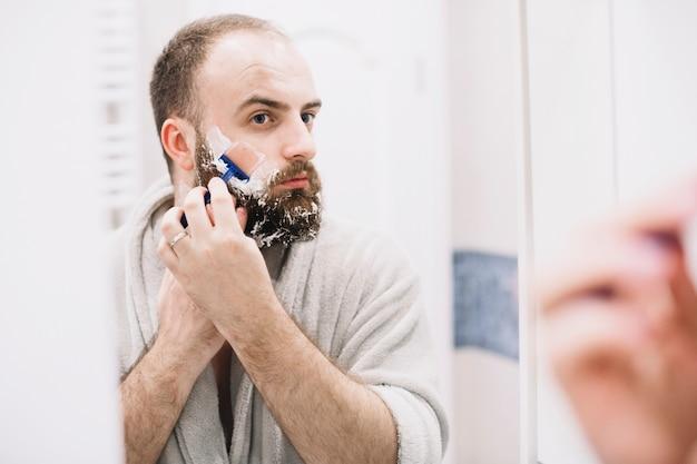 Gut aussehender mann, der am morgen rasiert