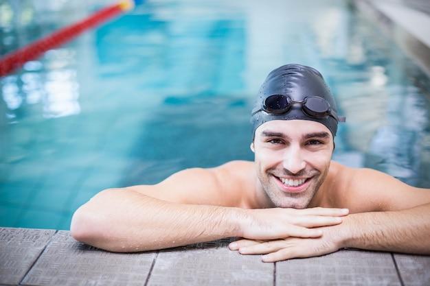 Gut aussehender mann, der am rand des pools stillsteht