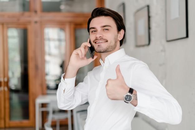 Gut aussehender mann, der am telefon im büro spricht