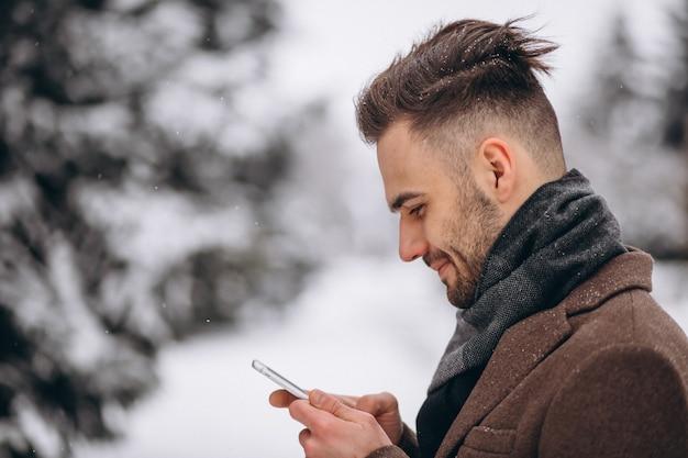 Gut aussehender mann, der am telefon in einem winterpark spricht