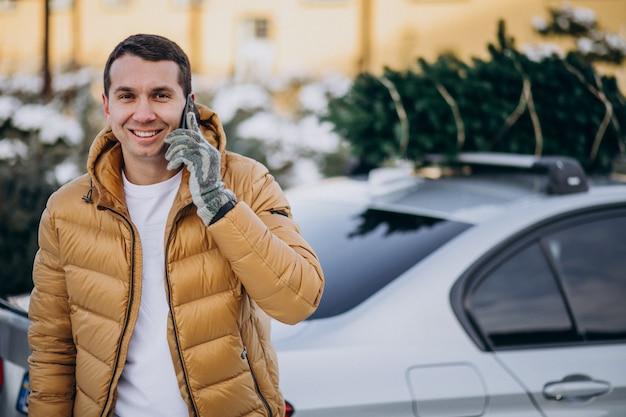 Gut aussehender mann, der am telefon mit dem auto mit weihnachtsbaum auf die oberseite spricht