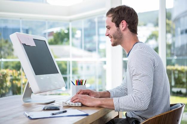 Gut aussehender mann, der an computer in einem hellen büro arbeitet