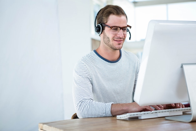 Gut aussehender mann, der an computer mit kopfhörer in einem hellen büro arbeitet