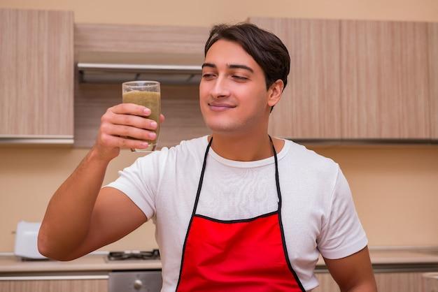 Gut aussehender mann, der an der küche arbeitet