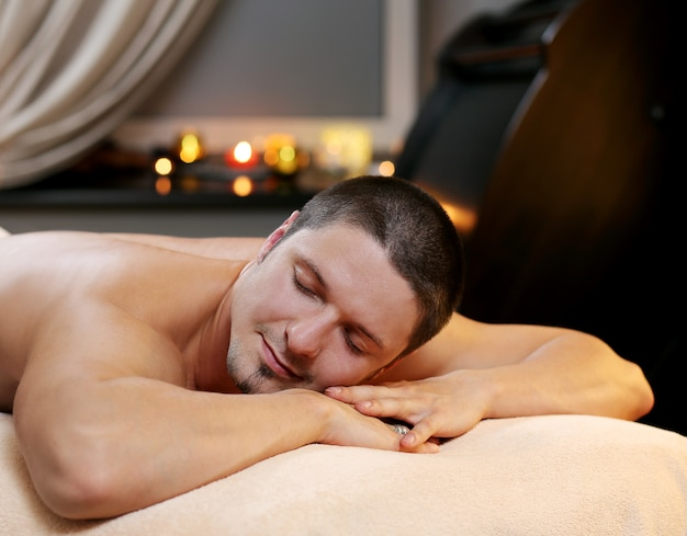 Gut aussehender mann, der an einem badekurort sich entspannt