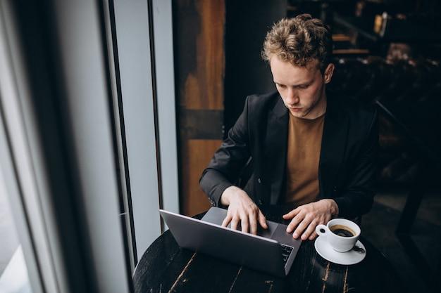 Gut aussehender mann, der an einem computer in einem café arbeitet und kaffee trinkt