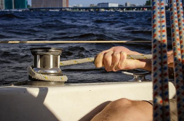 Gut aussehender mann, der an segelboot arbeitet. wassersport.