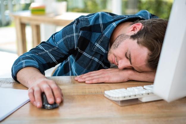 Gut aussehender mann, der auf computer in einem hellen büro schläft