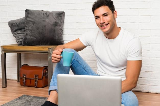 Gut aussehender mann, der auf dem boden mit seinem laptop sitzt