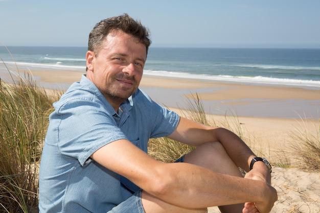 Gut aussehender mann, der auf dem strand, sitzend auf dem sand sich entspannt