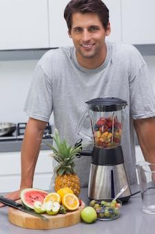 Gut aussehender mann, der auf dem zähler seiner küche sich lehnt