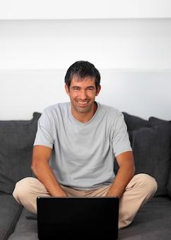 Gut aussehender mann, der auf der couch mit einem laptop sitzt
