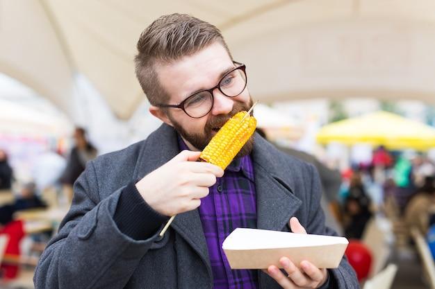 Gut aussehender mann, der auf der straße gerösteten mais isst.