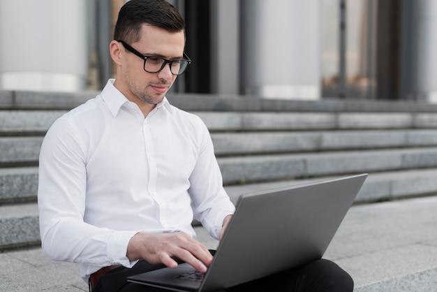 Gut aussehender mann, der auf laptop schaut