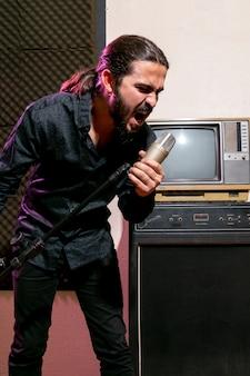 Gut aussehender mann, der auf mikrofon singt
