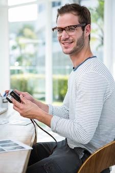 Gut aussehender mann, der bilder auf kamera in einem hellen büro betrachtet