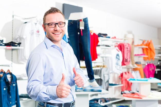 Gut aussehender mann, der blue jeans im shop oder im speicher kauft
