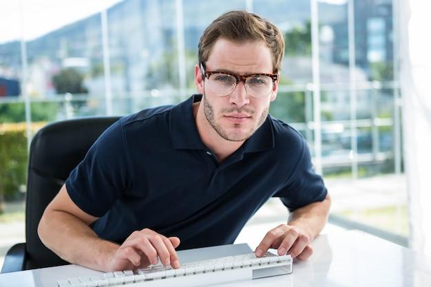 Gut aussehender mann, der computer im büro verwendet