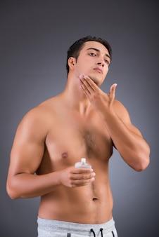 Gut aussehender mann, der das aftershave-afer-rasieren anwendet