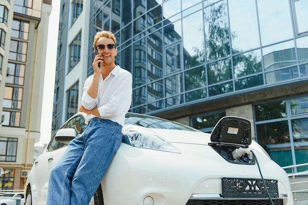 Gut aussehender mann, der das telefon benutzt, während das auto aufgeladen wird