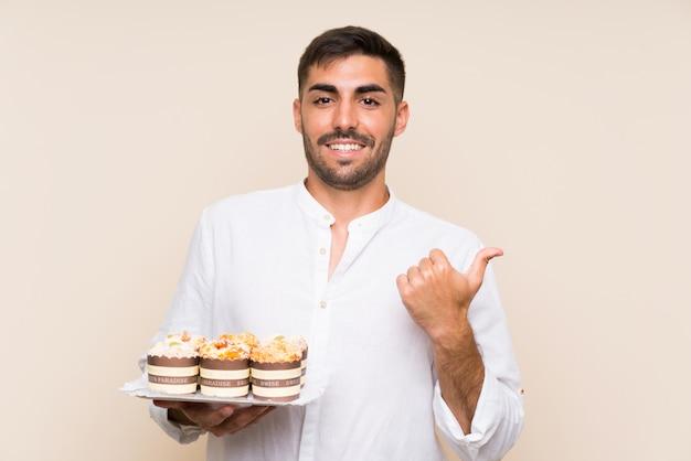 Gut aussehender mann, der den muffinkuchen zeigt auf die seite hält