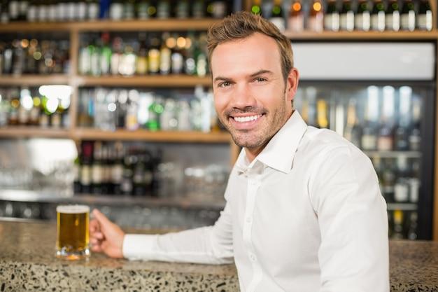 Gut aussehender mann, der ein bier hält