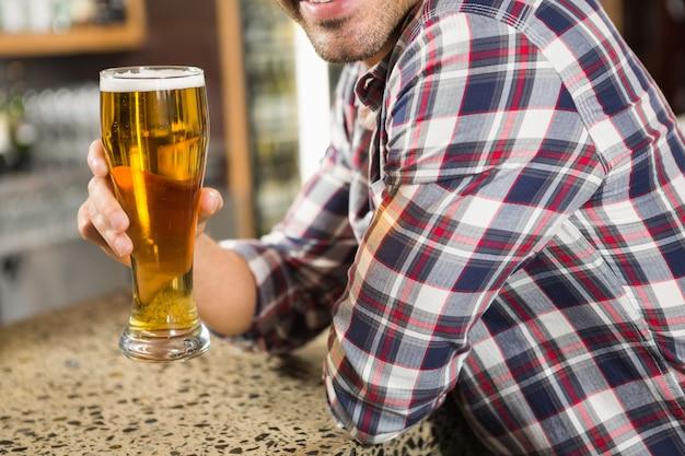 Gut aussehender mann, der ein bier trinkt