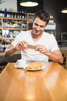Gut aussehender mann, der ein foto seines sandwiches macht