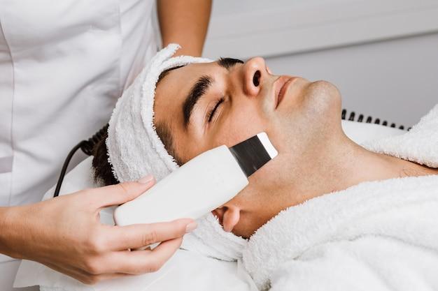 Gut aussehender mann, der ein gesichtspeeling mit ultraschallkavitation erhält. hautreinigungsverfahren im beauty-spa-salon.