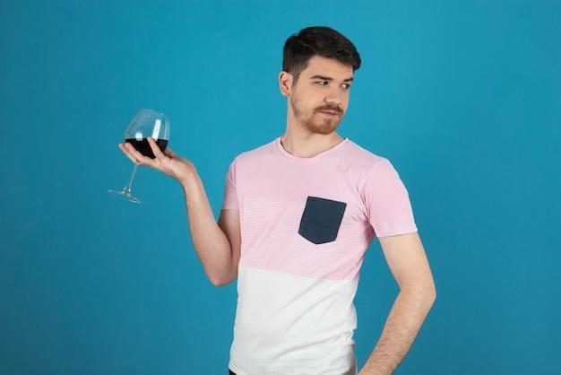 Gut aussehender mann, der ein glas wein hochhält und wegschaut.