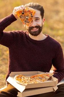 Gut aussehender mann, der ein stück pizza zeigt