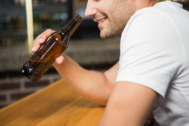 Gut aussehender mann, der eine flasche bier hält
