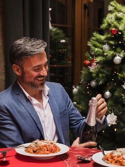 Gut aussehender mann, der eine flasche champagner hält