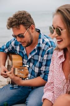 Gut aussehender mann, der eine gitarre spielt und ein lied für seine besten freunde singt