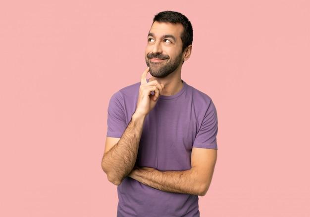 Gut aussehender mann, der eine idee beim auf lokalisiertem rosa hintergrund oben schauen denkt