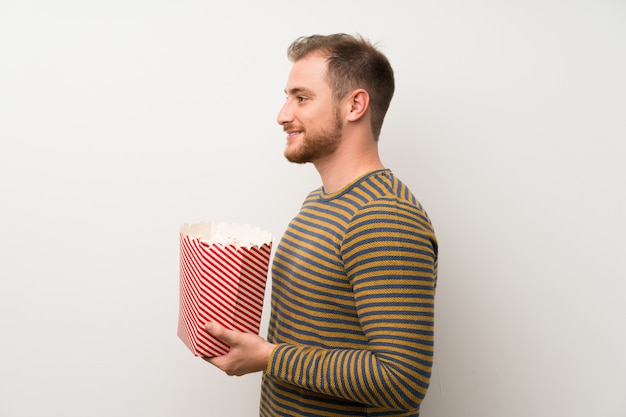 Gut aussehender mann, der eine schüssel popcorn hält
