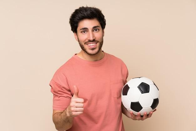Gut aussehender mann, der einen fußball hält