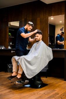 Gut aussehender mann, der einen neuen haarschnitt erhält