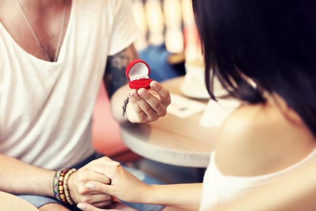 Gut aussehender mann, der einer schönen frau im café einen vorschlag macht Premium Fotos