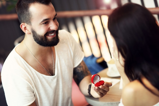 Gut aussehender mann, der einer schönen frau im café einen vorschlag macht