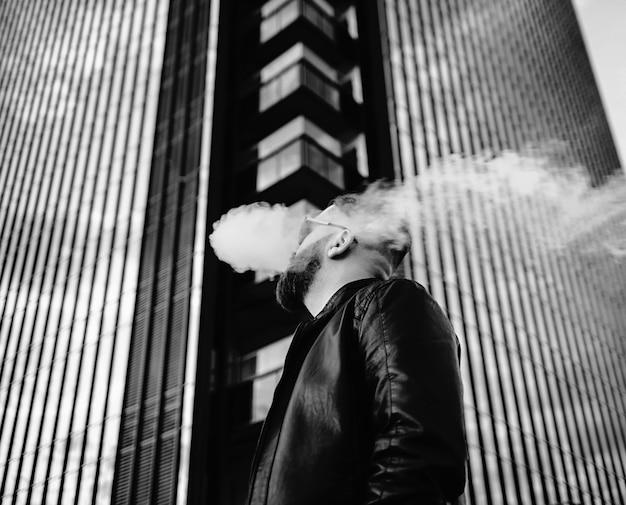 Gut aussehender mann, der elektronische zigarette vaping ist