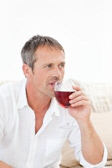 Gut aussehender mann, der etwas rotwein trinkt