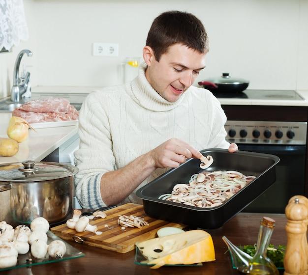 Gut aussehender mann, der fleisch mit pilzen kocht