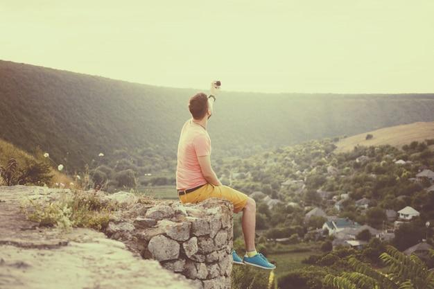 Gut aussehender mann, der fotos von ihm selbst mit aktionskamera macht. retro vintage instagram filter