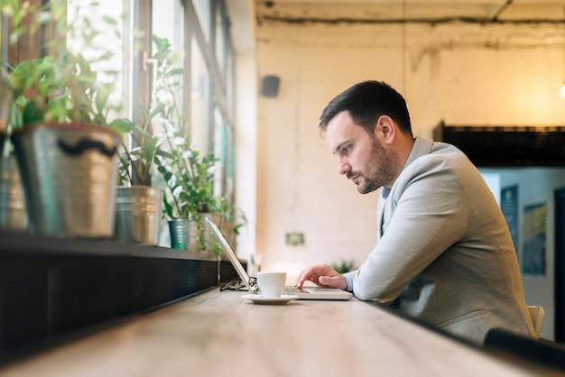 Gut aussehender mann, der front des laptops im café sitzt.