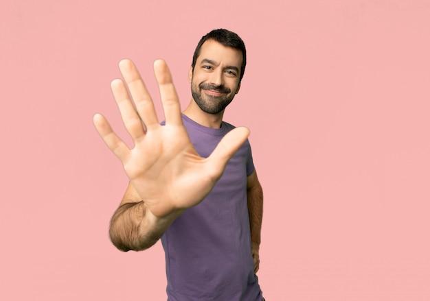Gut aussehender mann, der fünf mit den fingern auf lokalisiertem rosa hintergrund zählt