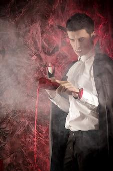 Gut aussehender mann, der für halloween in einem dracula-kostüm gekleidet ist, hält ein glas blut