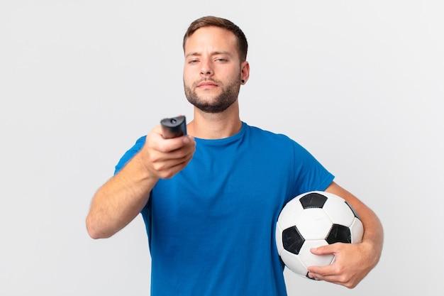 Gut aussehender mann, der fußball im fernsehen guckt