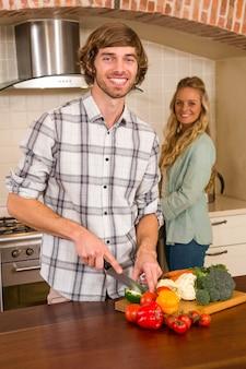 Gut aussehender mann, der gemüse mit freundin im hintergrund in der küche schneidet